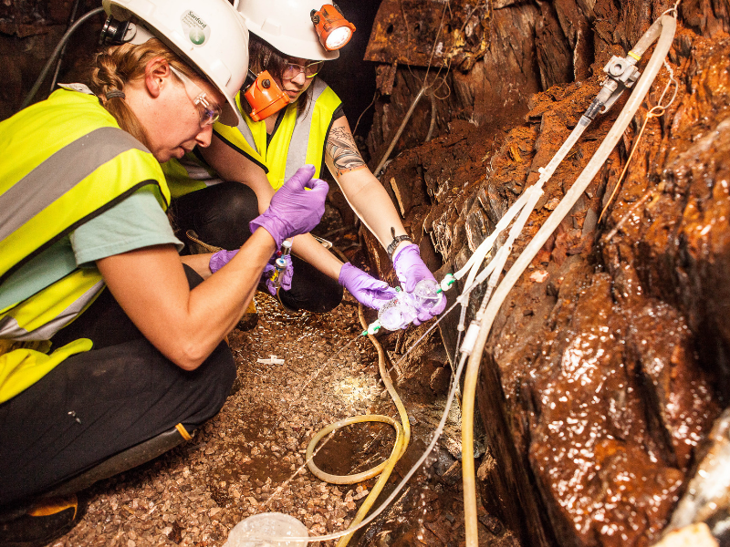 Brittany Kruger (left) of the Desert Research Institute, field coordinator for Casar's work at the Deep Mine Microbial Observatory in South Dakota, and Casar collect samples from a fluid fracture in a wall of the mine. (Photo credit: Matthew Kapust/Sanford Underground Research Facility)