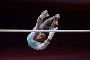 Gymnast Simone Biles twists through the air as she attempts to grab the uneven bars.